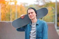 Skatebarder joven que presenta con el monopatín en el skatepark Concepto del deporte fotos de archivo libres de regalías
