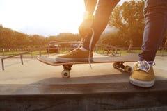 Skateboader hands tying shoelace on skateboard Stock Photos