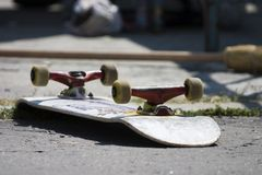 Skateboard. Overturned skateboard lying wheels up on the pavement Royalty Free Stock Images