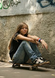 Skateboard. The girl with skateboard sitting against a wall stock photography