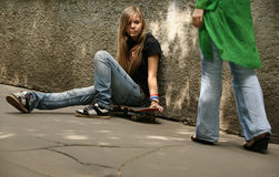 Skateboard. The girl with skateboard sitting against a wall Royalty Free Stock Images