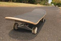 Skateboard on asphalt footpath Stock Photography