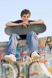 Skateboard boy. Portrait of teenager boy sitting on ramp with skateboard Royalty Free Stock Photo