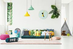Skateboard in colorful kid`s room. Skateboard and wooden stool on pink rug in colorful kid`s room interior with pouf and patterned pillows stock images