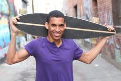 Skateboard fahren des attraktiven Sitz-Mannes, der städtische Gassen-Weise kreuzt Stockfotos