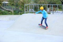 Skateboard fahren des Reitens der jungen Frau auf einem Skateboard Stockfotografie