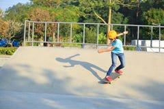 Skateboard fahren des Reitens der jungen Frau auf einem Skateboard Stockfotos