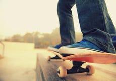 Skateboard fahren von den Beinen, die auf ein Skateboard fahren Stockfotografie