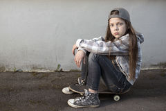 Skateboard girl resting. Streetwear style child girl resting on skateboard near blank concrete wall stock photography