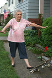 Skateboard Grandmother 2. Senior citizen woman standing on tilted skateboard with arms out royalty free stock photo