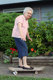 Skateboard Grandmother 3. Senior citizen woman with one foot on a skateboard royalty free stock photography