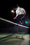Skateboard Hippie Jump. A young skaterboarder doing a Hippie Jump over a tennis net Stock Photo