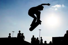 Skateboard jump. Jumping skateboarder on skateboard silhouette Stock Image