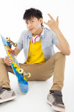 Skateboard man sitting and make a rock gesture Stock Photos