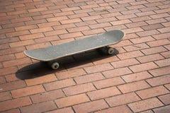 Skateboard op rode bakstenen Stock Foto