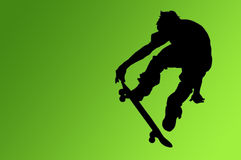 The Skateboard Rider. Silhouette of a boy on a skateboard isolated on a green gradient background with a clipping path Royalty Free Stock Photo