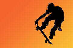 The Skateboard Rider. Silhouette of a boy on a skateboard isolated on an orange gradient background with a clipping path Stock Photo