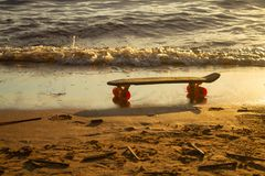 Skateboard in the sand on the beach at sunset stock image
