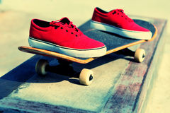 Skateboard and sneakers at skatepark Royalty Free Stock Images