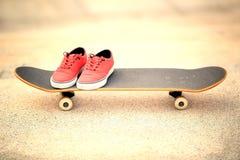 Skateboard and sneakers at skatepark Stock Photos