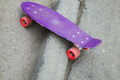 Skateboard stands on the curb of asphalt road Royalty Free Stock Image