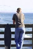 Skateboard or Surf. Teen at beach watching surfers Stock Photography