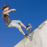 Skateboard tricks. Teen boy does tricks in the half pipe at a skate park Stock Photo