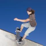 Skateboard tricks. Teen boy does tricks on  half pipe at a skate park Stock Image