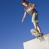 Skateboard tricks. Teen boy dives into skate park on his skateboard Royalty Free Stock Photography