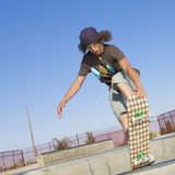 Skateboard tricks. Teen boy does tricks in the half pipe at a skate park Royalty Free Stock Image