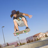 Skateboard tricks. Teen boy does tricks in the half pipe at a skate park stock photo