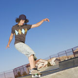 Skateboard tricks. Teen boy grinds on the top of a half pipe at a skate park Royalty Free Stock Image