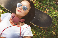 Skateboardavkoppling vilar liggande kyligt Headphonebegrepp fotografering för bildbyråer