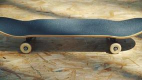 Skateboarden med vit rullar på en träbakgrund i en skatepark arkivfilmer