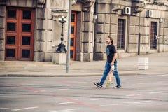 Skateboarder που διασχίζει το δρόμο στις οδούς πρωτευουσών Στοκ Εικόνες