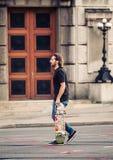 Skateboarder που διασχίζει το δρόμο στις οδούς πρωτευουσών Στοκ εικόνα με δικαίωμα ελεύθερης χρήσης