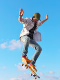 Skateboarder. Jumps in town park on background sky with cloud Stock Photography