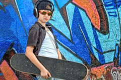 Skateboarder. Portrait of a trendy boy teenager with headphones and skateboard outdoors Stock Images