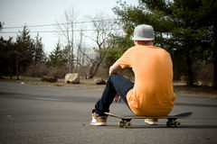 Skateboarder. A young skater resting on his board Royalty Free Stock Photography