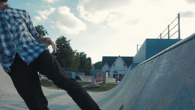 Skateboarder in action on a ramp, doing stall trick, rock to fakie on skateboard stock footage
