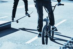 Skateboarder and bicycler. Blue toning. Skateboarder and bicycler. Active recreation. Blue toning royalty free stock image
