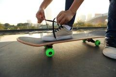 Skateboarder bindende schoenveter op stad Royalty-vrije Stock Foto's