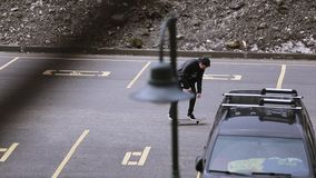 Skateboarder in cap riding on parking space, make trick. Skateboard. Extreme stock video footage