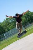 Skateboarder che fa i trucchi su suo fotografia stock