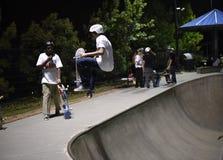 Skateboarder che fa trucco allo skatepark Fotografia Stock