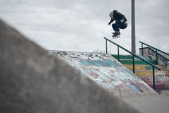 Skateboarder che fa un Ollie sopra la ferrovia in uno skatepark Immagini Stock Libere da Diritti