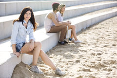 Skateboarder che si siedono sui punti alla spiaggia fotografie stock libere da diritti