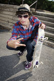 Skateboarder crouching down making peace sign. And holding his board Stock Photo