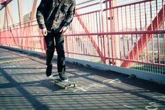 Skateboarder cruise on bridge Stock Images