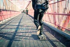 Skateboarder cruise on bridge Stock Photos